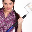 Woman holding up a paint roller — Stockfoto