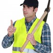 Labourer carrying pickaxe — Stock Photo #14273379
