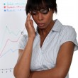 Stressed businesswoman standing by a flip chart — Stock Photo #14274157