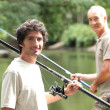 Men fishing at a lake — Stockfoto