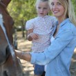 Mother and daughter stroking horse — Stock Photo