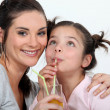 Mother and daughter drinking through straws — Stock Photo #14274599