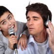 Father and son singing into a microphone - Stock Photo