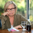 Stock Photo: Unhappy womstaring down at her pills