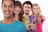 Students in a row giving the thumb up. — Stock Photo
