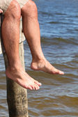 Close-up of legs of a man sitting on a pontoon — Stock Photo