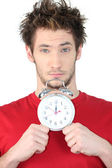 Young guy with swollen eyes showing alarm clock — Stock Photo