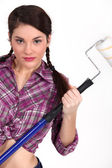 Woman holding up a paint roller — Stock Photo