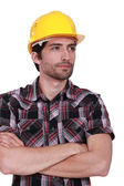 Portrait of handsome craftsman with safety helmet standing cross-armed — Stock Photo