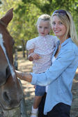Mother and daughter stroking horse — Stockfoto