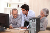 Young helping senior with computer — Stockfoto