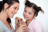 Woman sharing a glass of juice with her little sister — Stock Photo