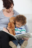 A mother reading to her son. — Stock Photo