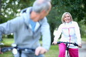 Older couple on bikes — Stock Photo