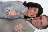 Mature couple thumbs up and all smiles — Stock Photo