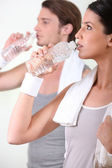 A couple drinking water after sport — Stock Photo