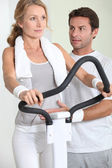 Portrait of a woman on exercise bike with coach — Stock Photo