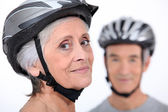 Older couple wearing cycling helmets — Stock Photo