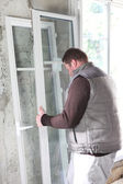 Worker laying windows in house under construction — Stock Photo