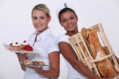 Two bakery worker holding food — Stock Photo