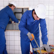 Foto Stock: Two plumbers hard at work