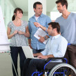 Man in a wheelchair working in an office — Stock Photo