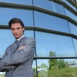 Young businessman standing in front of a building — Stock Photo