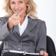 Smiling businesswoman pointing her pen at the camera — Stock Photo