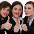 Three businesswomen giving the thumbs-up - Stock Photo