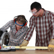 Man and woman using circular saw - Stock Photo