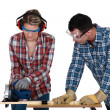 Tradespeople cutting a wooden plank with a circular saw — Stock Photo