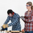 Woman supervising carpenter - Stock Photo