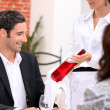 Stock Photo: Wine waitress showing wine bottle to customer