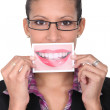 Woman holding up an enlarged picture of her mouth — Stock Photo #14556293