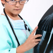 Little boy dressed as a doctor looking at a x-ray image - Stock Photo