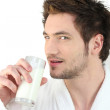 Man in dressing gown drinking milk — Stock Photo #14557313
