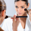 Brunette applying blusher in the mirror — Stock Photo