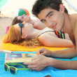 Couple on the beach with magazine — Stock Photo