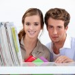 Young couple in library - Stock Photo
