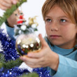 Little boy hanging decorations on Christmas tree — Stock Photo #14558657