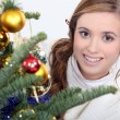 Young woman decorating Christmas tree — Stock fotografie