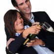 Happy couple pouring champagne — Stock Photo