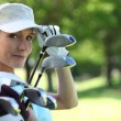 Woman with golf clubs — Stock Photo