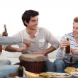 Three male friends playing instruments - Stock Photo