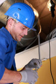 Electrician working by exposed ceiling panel — Stock Photo