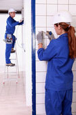 Electricians working in a tiled room — Foto Stock