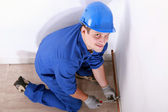 Young craftsman kneeling and screwing a copper pipe, picture taken from the bottom — Stock Photo