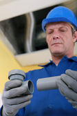 Plumber fixing replacement pipe — Stock Photo