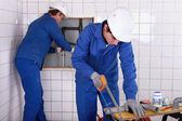 Two plumbers hard at work — Stock Photo