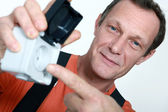 Electrician holding an exterior wall socket — Stock Photo